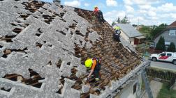 megrongálódott tetőn dolgozik az önkéntes tűzoltó