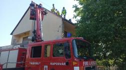 létráról avatkoznak  be a tűzoltók, bontják a tetőt