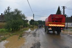 kötél egyesület teherautója áll az úton, háttérben az elöntött falu
